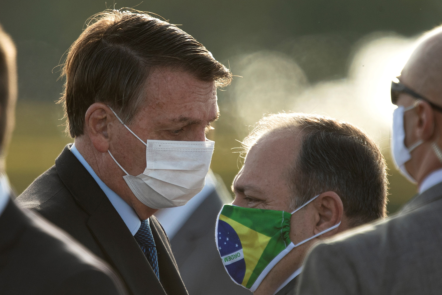 The President of Brazil Jair Bolsonaro (L) speaks with acting Minister of Health Eduardo Pazuello during the raising of the national flag, in the Palacio do Alvorada, in Brasilia, Brazil, 09 June 2020. The Brazilian Supreme Court determined that the Government must re-disclose the daily data of the pandemic of the new coronavirus in a consolidated manner, as it had been doing until last Thursday, before adopting a new and controversial methodology, and gave a period of 48 hours to explain that decision. EFE/ Joedson Alves